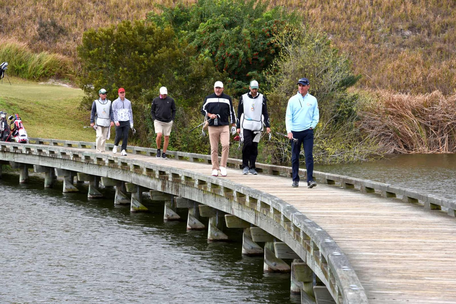 Golfers walking over water on course bridge